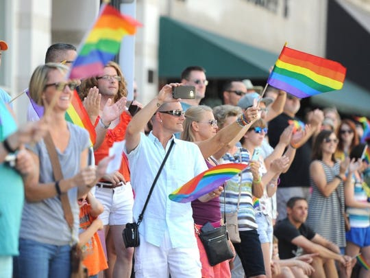 Spectators applaud and take photos on Gay St. during the 2016 Knoxville PrideFest Parade on Saturday, June 18, 2016.