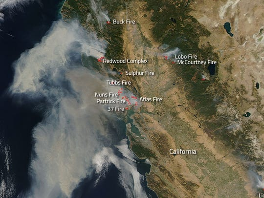 A NASA satellite captured this image of the wildfires in California on Oct. 9, 2017. Actively burning areas are outlined in red.