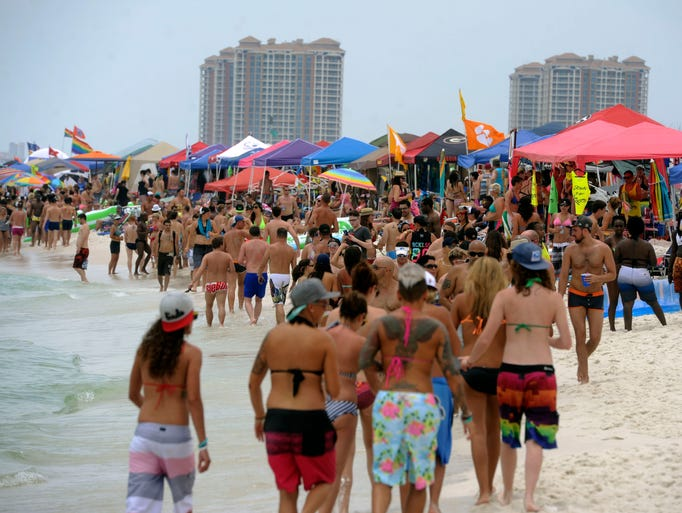 Vacationers stroll along the beach at Park East Saturday afternoon.