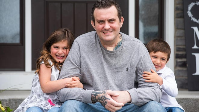 Nick Falvo sits with his daughter Gianna, 6, and son Nicholas, 4, at their Goshen home. Nick was put in a medically induced coma for 33 days during his battle with COVID-19.