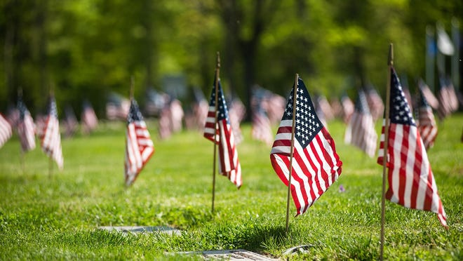 Nam Knights and volunteers placed American flags on veterans graves for Memorial Day at the Orange County Veterans Memorial Cemetery in Goshen on Friday.