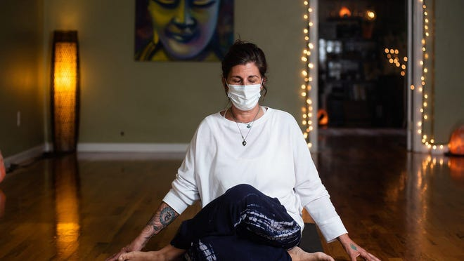 Charlene Predmore, owner of Happy Buddha Yoga poses for a portrait at her yoga studio in Goshen, NY on Monday, May 18th, 2020. On March 15th, along with thousands of others, Charlene Predmore's livelihood came to a halt, but with the help of meditation and family, she's making it through the COVID-19 pandemic and shutdown. Predmore, a yoga instructor and owner of Happy Buddha Yoga in the village of Goshen, tries to keep a schedule and visits her studio everyday to practice in solitude. Lighting incense as she starts her day, she tries to stay hopeful declaring that