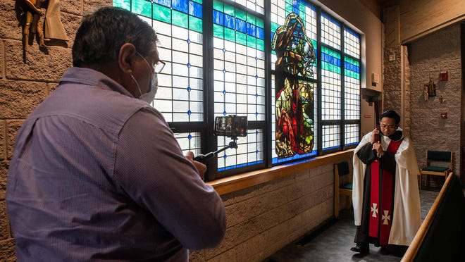 Knight of Columbus member Michael Martin, right, uses Facebook to livestream Assistant Father Anthony Trung as he walks the stations during a Stations of the Cross Mass at Our Lady of Mount Carmel church in Middletown on April 10, 2020.