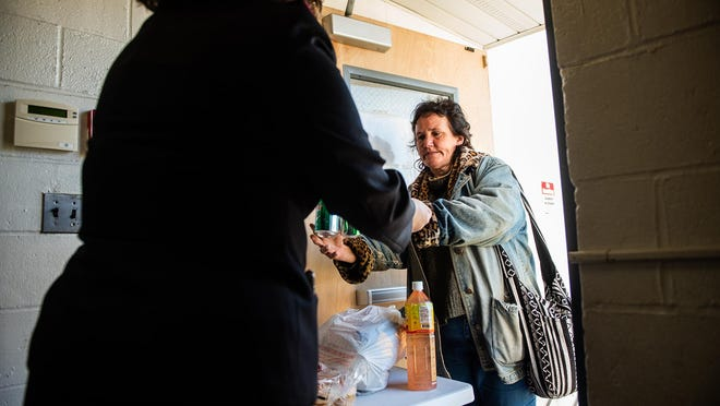 Lt. Samantha Keaton gives two cans of soda to local aid recipient Ann Marie Sullivan at the Salvation Army Church and Service Center in Middletown on Friday.