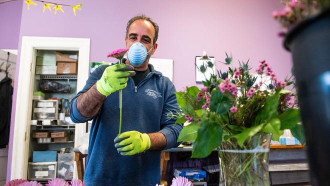 David Recine, owner of Flowers by David Anthony, works alone on a delivery order in his shop in Highland Mills on Thursday.
