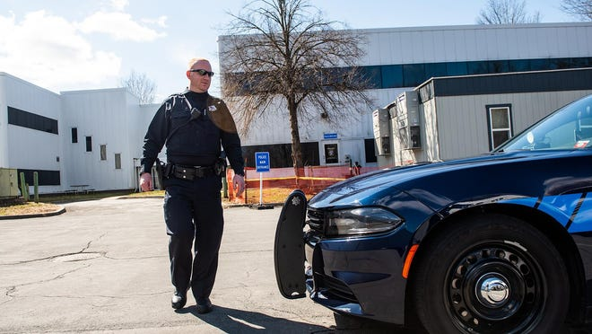 Montgomery police Officer Kevin Greany walks to his squad car on Saturday. Some local police say although it's still early, they're seeing a drop in reported crime amid the coronavirus pandemic.