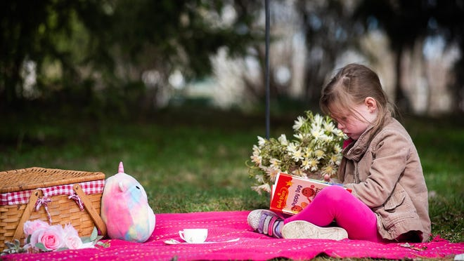 Scarlett Sullivan, 5, reads to her stuffed unicorn at her home in Walden on Thursday during East Coldenham Elementary School's virtual spirit week. [PHOTOS BY KELLY MARSH/FOR THE TIMES HERALD-RECORD
