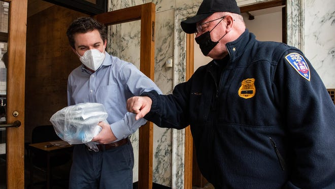 Sen. James Skoufis elbow bumps Chief of the Walden Police Department Jeff Holmes as he delivers a bag of gloves and masks at Skoufis's office in Newburgh on Monday. Skoufis's office provided masks and gloves to at-risk communities and essential workers.