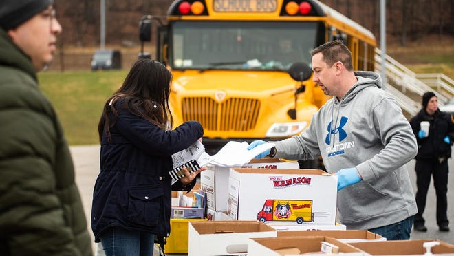 Presidential Park Elementary School assistant principal Matt Kelly, right, hands out enrichment packets to parents for students during the resource drive at the school in Middletown. The district has provided students with packets with course work and books while schools remain closed due to COVID-19.