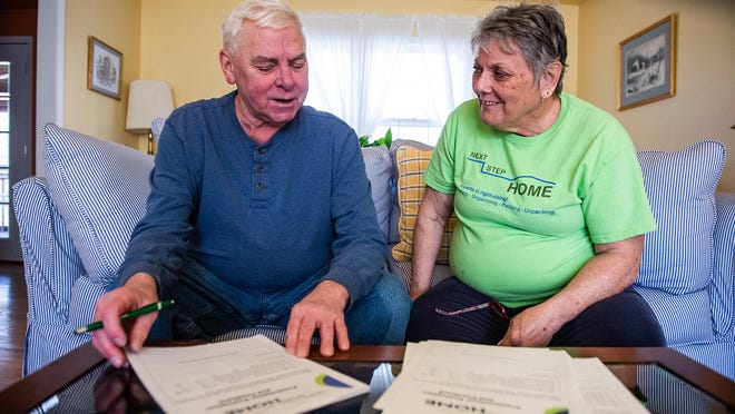 John Mountford, left, and Colleen Mountford, right, owner of Next Step Home, review some of the paperwork clients sign after an initial meeting. Next Step Home is a business that helps older clients downsize and prepare  them for their next move.