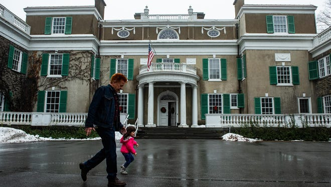 Richard Painter of Jersey City, NJ, left, and Emma Feltes 3 of Garrison, right, walk in front of Springwood, the home of President Franklin D. Roosevelt during the holiday open house at the Franklin D. Roosevelt Presidential Library and Museum and the Home of FDR National Historic Site in Hyde Park, NY on Saturday, December 14th, 2019.