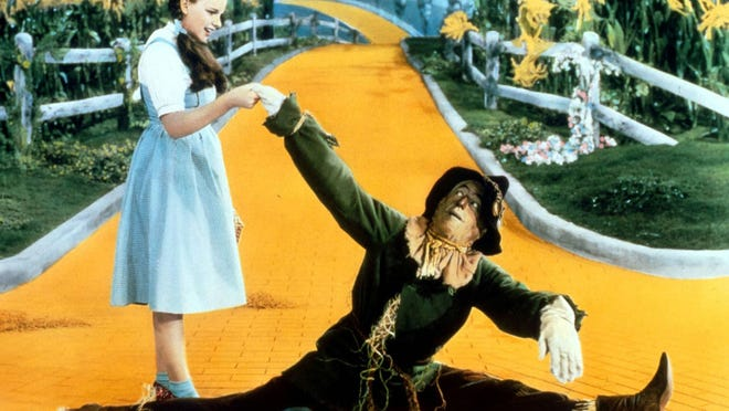 Dorothy (Judy Garland) and her straw-stuffed friend the Scarecrow (Ray Bolger) begin their trip down the Yellow Brick Road.   photos by MGM A scene from the 1939 classic THE WIZARD OF OZ.  Pictured from left: Judy Garland (Dorothy), Ray Bolger (Scarecrow). Credit: MGM
