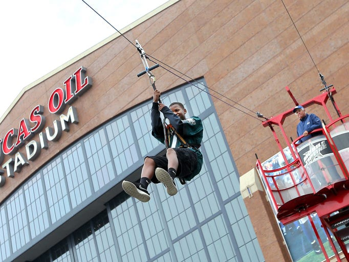 Thirteen-year-old Derin McCulley of Indianapolis flies down the zip line in the fan zone located in front of Lucas Oil Stadium before the start of Monday's game against the Philadelphia Eagles on September 15, 2014.