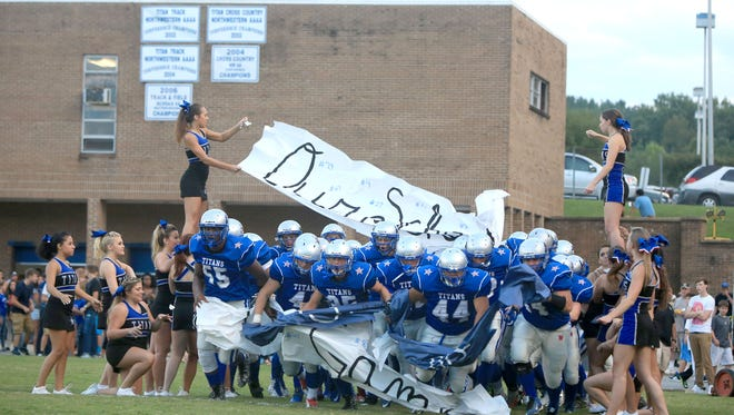 McDowell football players bust through a banner prior to a 2015 home game.