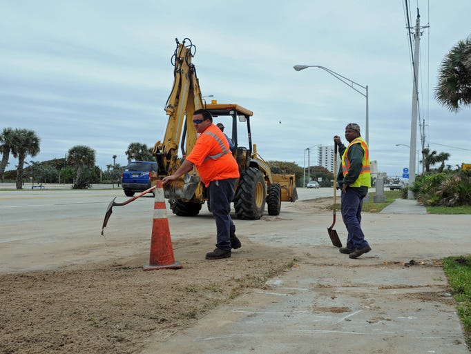 Louis Molina, left, and Larry Phillips, workers for the City of Melbourne, continue cleanup at the spot where a water main broke, causing a boil water alert for areas around Indian Harbour Beach and Satellite Beach.