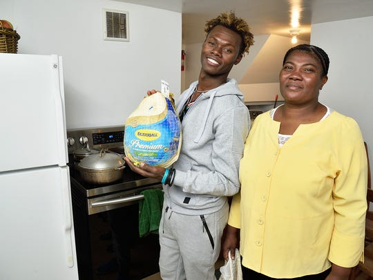 Haitian immigrant Jean Radyn Piard (L) and his aunt Marie Venite Piard in the kitchen of their home in Teaneck. Jean will be celebrating his first Thanksgiving in the US this year. The Record Newspaper presented them with a turkey.