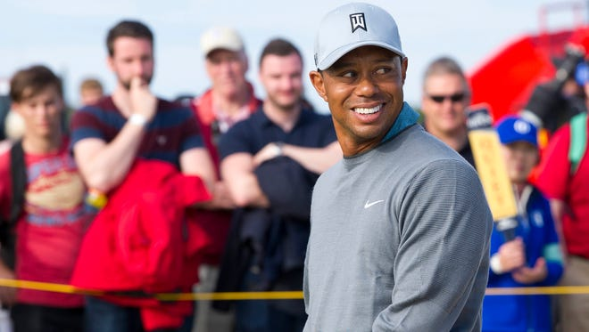Tiger Woods smiles while playing a practice round in preparation for the Open Championship