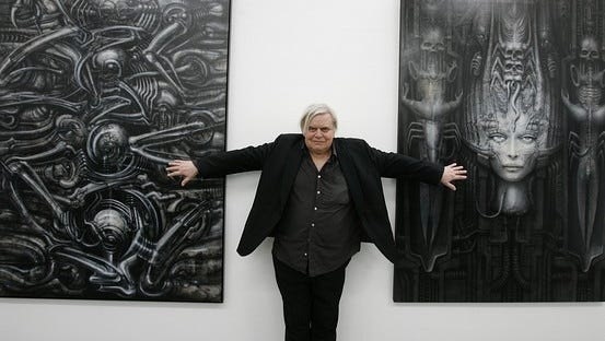 H.R. Giger poses with two of his works at a museum in Chur, Switzerland.