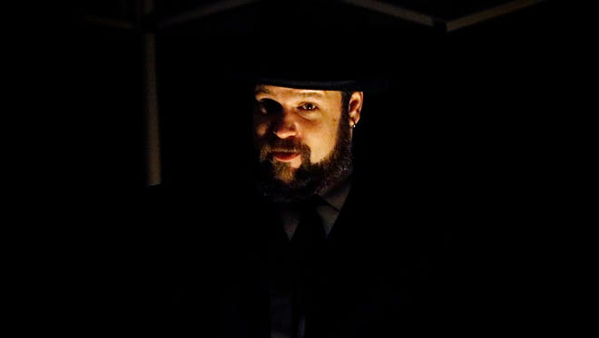 Alan Caum, of Athens, Pennsylvania, plays the role of Truckson LaFrance Friday night during the Chemung Valley History Museum's annual ghost walk at Woodlawn Cemetery.