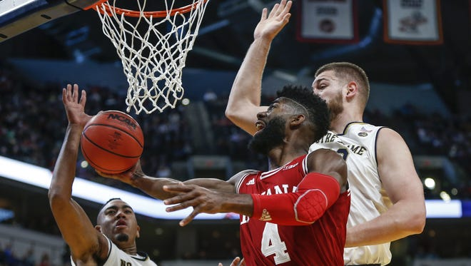 Indiana Hoosiers guard Robert Johnson (4) gets around two Notre Dame Fighting Irish defenders for the shot and make during the Crossroads Classic at Bankers Life Fieldhouse in Indianapolis on Saturday, Dec. 16, 2017.