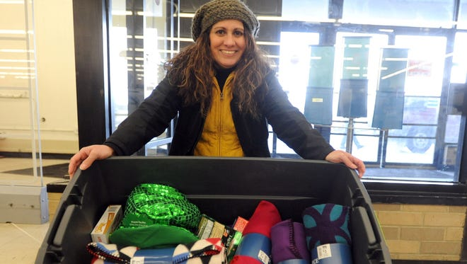 """Maria Edler, one of two Ohio State University at Marion students spearheading a homeless backpacks drive, shows a bin of items that have been collected at the Big Lots store in Marion. The """"Backpacks for the Homeless of Delaware and Marion Counties"""" campaign is collecting hygiene items, fleece blankets, gloves, scarves and nonperishable food items to fill backpacks for the homeless."""