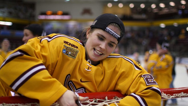 Minnesota's Dani Cameranesi cuts a piece of the net after Minnesota defeated Harvard, 4-1, in the women's college hockey tournament championship game on March 22, 2015, in Minneapolis.