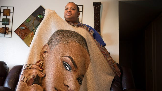 Carla Dean, mother of Ashley Nicole Metz, wears a blanket with the image of her murdered daugher in Lafayette Tuesday, July 11,  2017. Metz was killed in June 2016, in a car fire, without a clear motive.