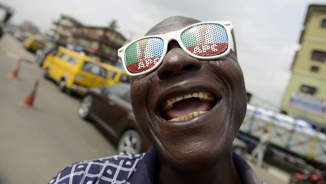 A man wears sun glasses branded with the  opposition All Progressives Congress during a rally christened Walk for Change in Lagos, on March 7, 2015, to drum up support for its presidential candidate Mohammadu Buhari.