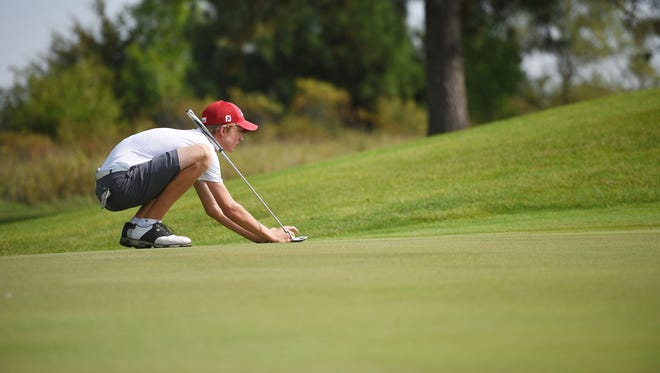 Lincoln's Nash Stenberg gets aligned with the ball during the 2017 boys high school golf city meet. Stenberg holds an 11-stroke lead at this year's event.
