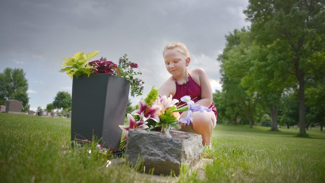 Jenna Jensen, 8, goes with her family to Woodlawn Cemetery to drop off flowers at baby's graves Friday, May 25, in Sioux Falls. Jensen goes with her parents about once a month to drop off flowers. She wants to make sure babies weren't forgotten.