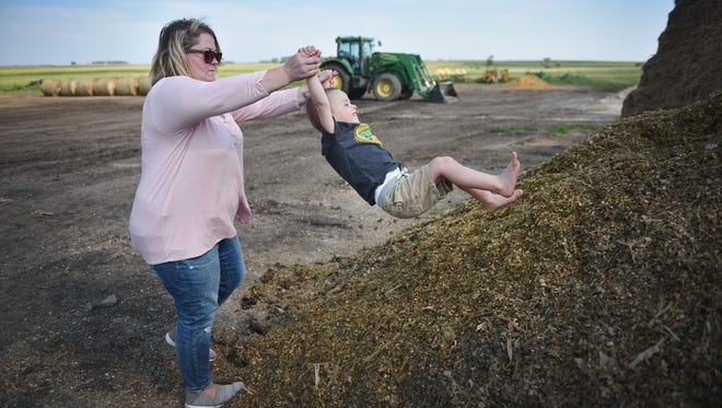 Morgan Kontz plays with her son Elijah, 3, on the family farm Wednesday, Aug 8, in Colman. Morgan Kontz and her husband run the family farm. They both work on the farm full time.