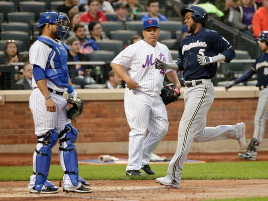 Milwaukee Brewers' Hector Gomez (5) runs past New York Mets starting pitcher Bartolo Colon (40) and catcher Johnny Monell to score on a hit by Carlos Gomez during the third inning of a baseball game Friday, May 15, 2015, in New York. (AP Photo/Frank Franklin II)