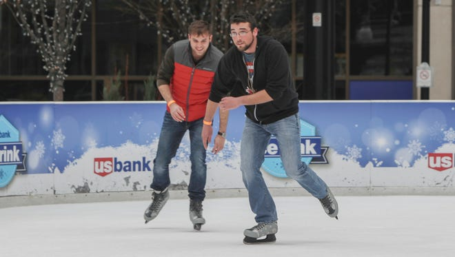 Coery Flaugher, 27, and Kyle Flaugher, 24, roll up their sleeves on the ice rink at Fountain Square during the warmer temperatures in Cincinnati on Christmas day.