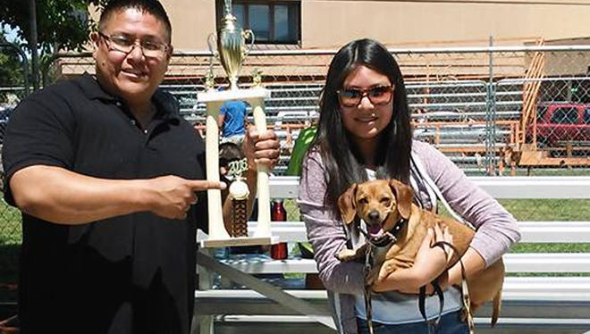 From left, Elton Benally and Asjah Benally pose on May 28 with Ginger, their 5-year-old dachshund who won the wiener dog race during Riverfest at Berg Park in Farmington. Ginger also placed first last year and finished in second place in 2014. She is also owned by Elton and Lucy Benally, of Bloomfield, and Asjah Benally, of Kirtland, as well as other family members. She enjoys going for walks in the park and loves little kids, according to her owners.