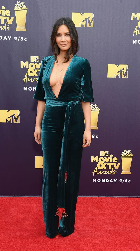 Actress Olivia Munn smiled for cameras in a velvet jumpsuit.