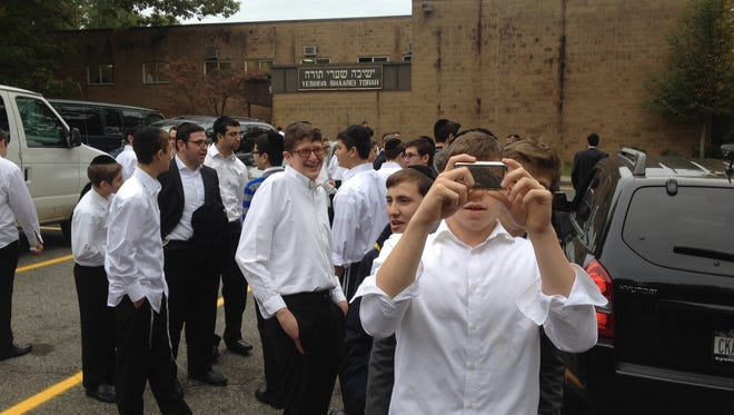 Students stand outside Yeshiva Shaarei Torah in Monsey, N.Y., a school the FBI raided late Wednesday night in connection with an investigation into a gang that pressured men into giving their wives religious divorces.