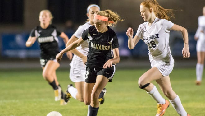 Jennifer Seward (8) moves the ball past Katelyn Stahl (16) during the Navarre vs Gulf Breeze soccer game at Gulf Breeze High School on Thursday, December 15, 2016.