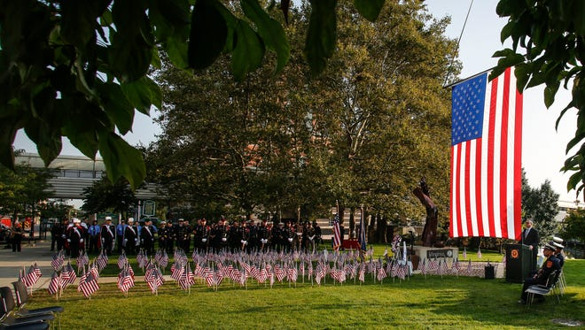 Kevin Sehlmeyer, State Fire Marshal and Director of the Bureau of Fire Services, right, speaks Monday morning, Sept. 11, 2017, at the 9/11 Memorial at Wentworth Park in downtown Lansing.'