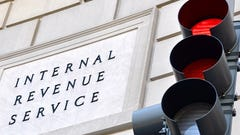 A red light is seen in from of a sign for the Internal Revenue Service.