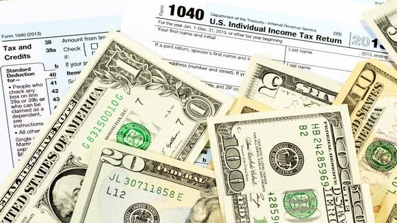 US Tax forms with money scattered on top.