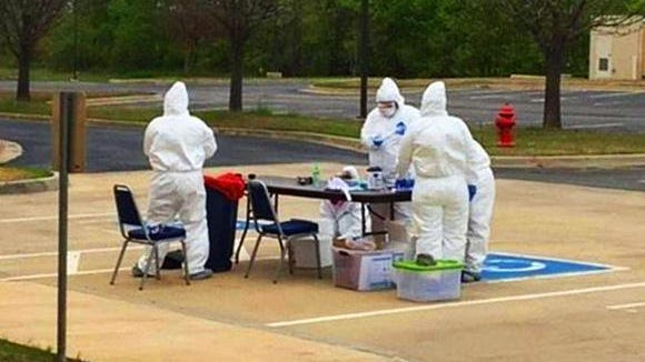 Health workers in full personal protective equipment at an Ardmore drive-thru test site on April 2. Health officials say confirmed cases of COVID-19 are tallied to a patient's home county and not the test site's county.