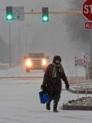 A pedestrian makes her way in Bismarck, N.D., Monday, March 5, 2018, as snow falls. Freezing rain, heavy snow and strong winds are blowing into the northern Plains, impacting travel, schools and government offices.