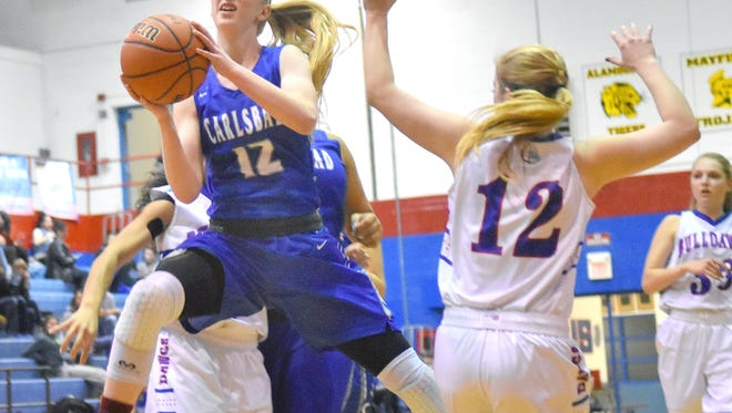 Carsyn Boswell splits two Las Cruces High defenders as she goes in for a layup Tuesday night in Las Cruces.