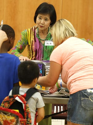 Shin Ae Zeigler hands out notebooks Saturday morning, Aug. 22 at the Boys and Girls Club of Fond du Lac, during the Back to School Fond du Lac program. More than 1,200 students were provided with necessary school supplies.