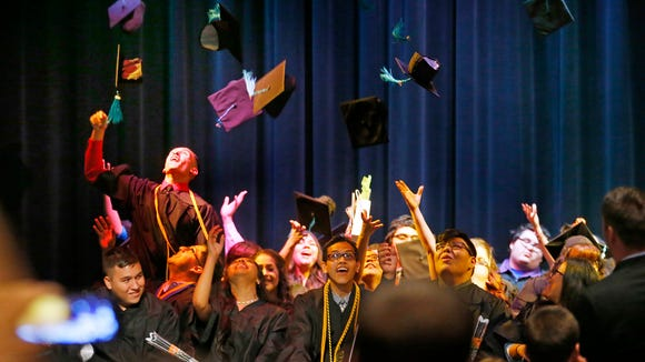 Graduates throw their hats into the air during the first graduation ceremony for Phoenix Collegiate Academy Tuesday, May 24, 2016, in Phoenix. Seven years ago, Rachel Bennett Yanof went door to door in a poor neighborhood in South Phoenix and promised parents that if they sent their kids to her new charter school, they would go to college. Every one of the 25 students in her senior class, is going to college or to some sort of higher education.