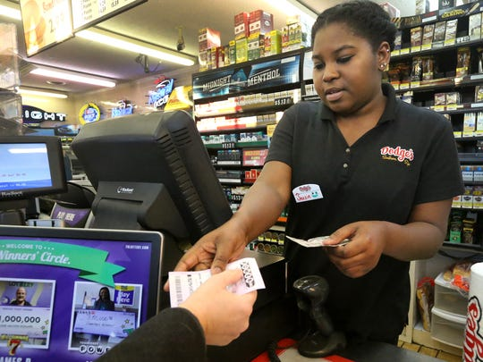 Jazzie Bowmen hands a Powerball ticket to a customer at Dodge's Stores on Monday, Jan. 11, 2016.