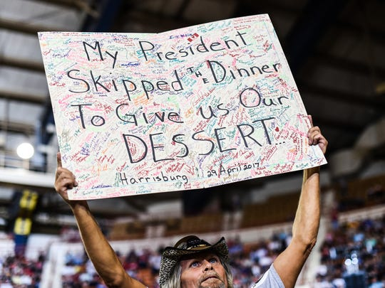 """A Trump supporter holds a sign that reads """"My President Skipped The Dinner To Give Us Our Dessert"""" referring to the White House Correspondents Dinner as President Donald Trump held a rally at the Farm Show Complex in Harrisburg on Saturday, April 29, 2017, the 100th day of his presidency."""
