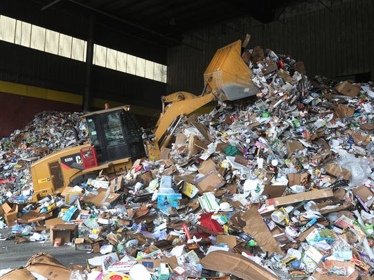 Piles of recycled items are moved into large piles