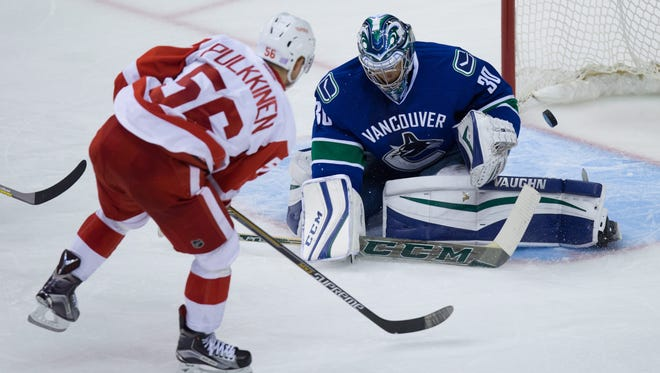 Detroit Red Wings' Teemu Pulkkinen, left, of Finland, scores against Vancouver Canucks' goalie Ryan Miller during the third period of an NHL hockey game Saturday, Oct. 24, 2015, in Vancouver, British Columbia.