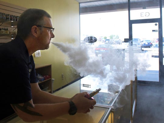 SS Vape District Manager Jason Goins vapes in the store